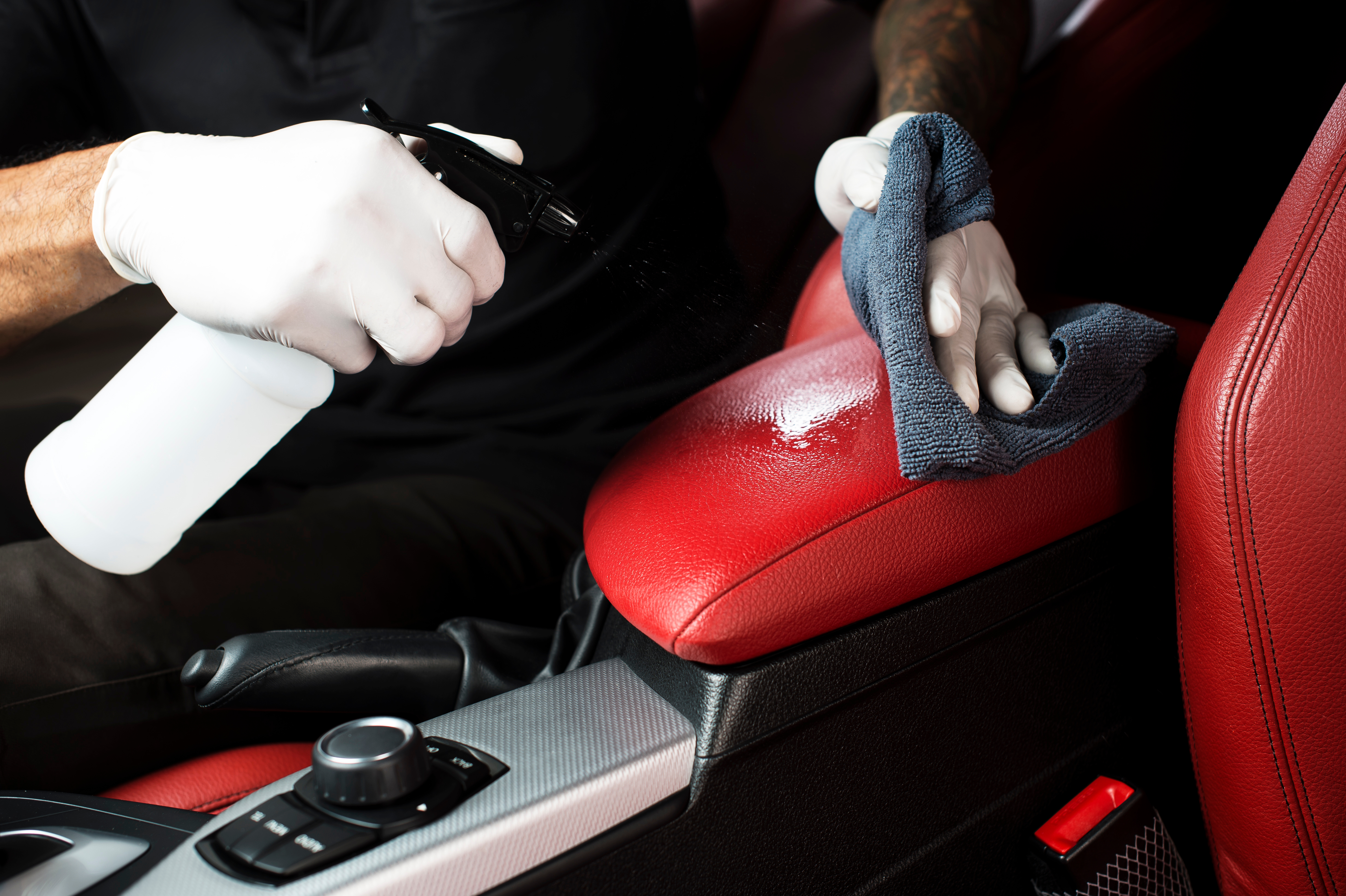 Red and black car interior being cleaned
