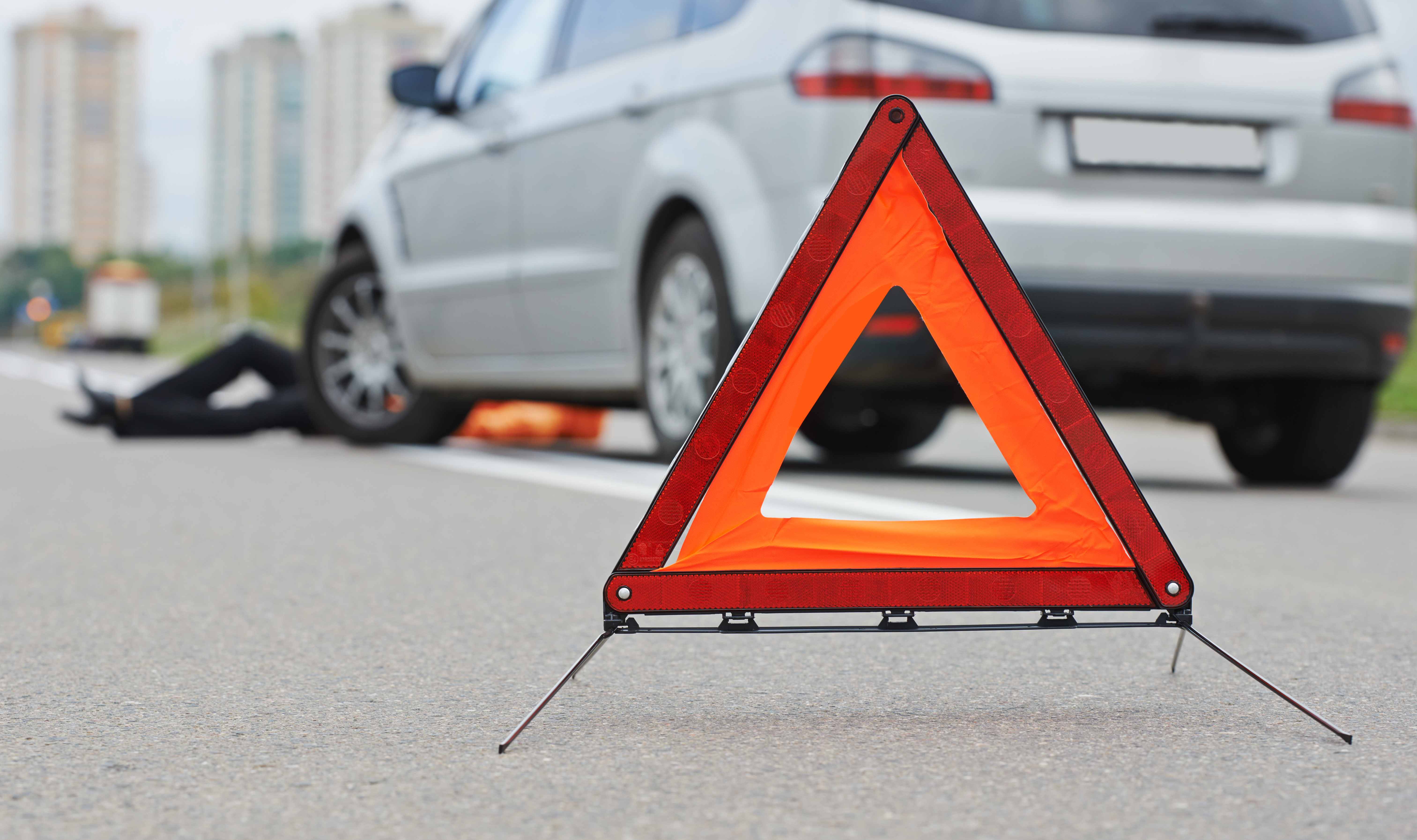 Pop up roadside warning cones with an out of focus car on the side of the road