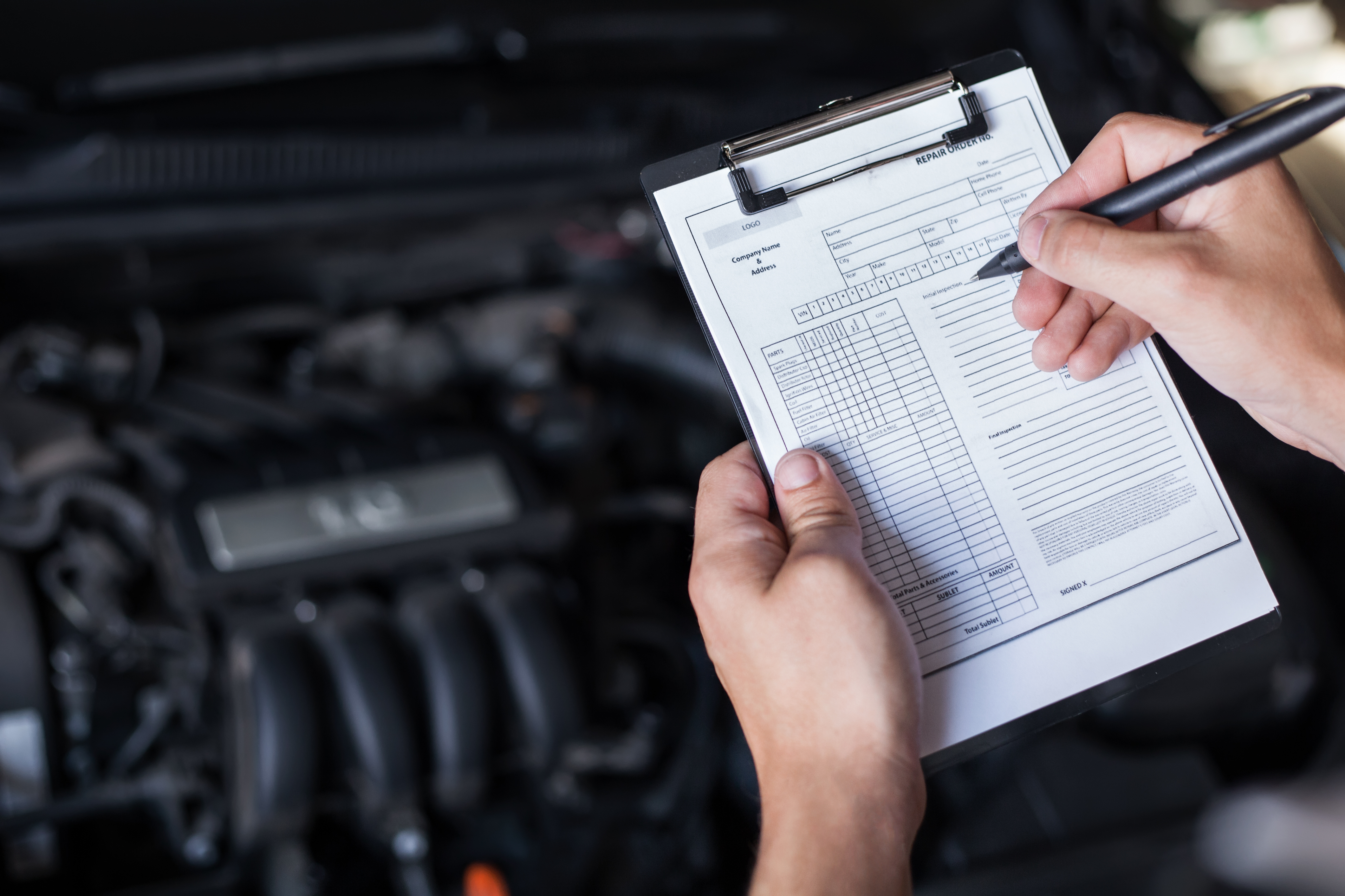 Vehicle inspection checklist with car engine in background